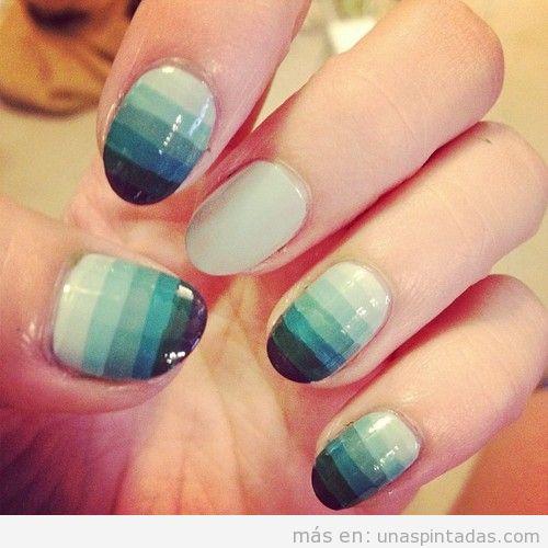 Diseño de uñas con un degradado de blanco roto a azul marino a rayas