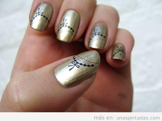 Diseño de uñas con color dorado metálico y dibujos lazos