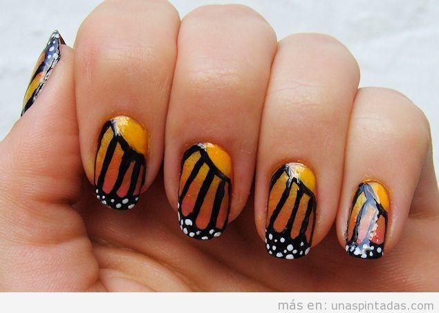 Decoración de uñas con dibujo de alas de mariposa naranja y negra
