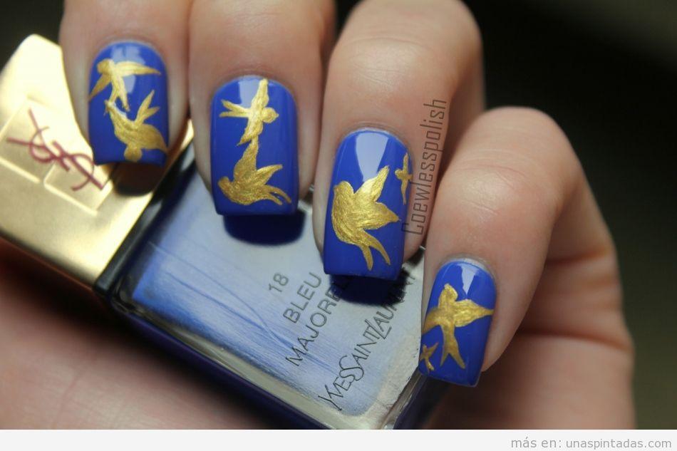 Decoración de uñas con dibujo de pájaro dorado sobre fondo azul