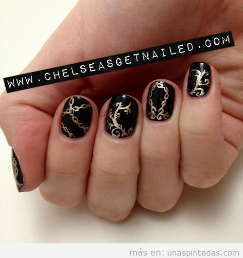 Diseño de uñas en negro y dorado con estampado barroco