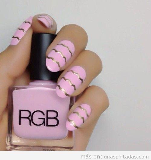 Decoración de uñas en rosa con ondas doradas