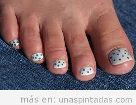 Diseño de uñas de los pies en blanco y lunares verdes