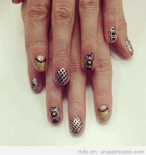 Decoración de uñas en dorado y negro con motivos geométricos, ideal para fiestas